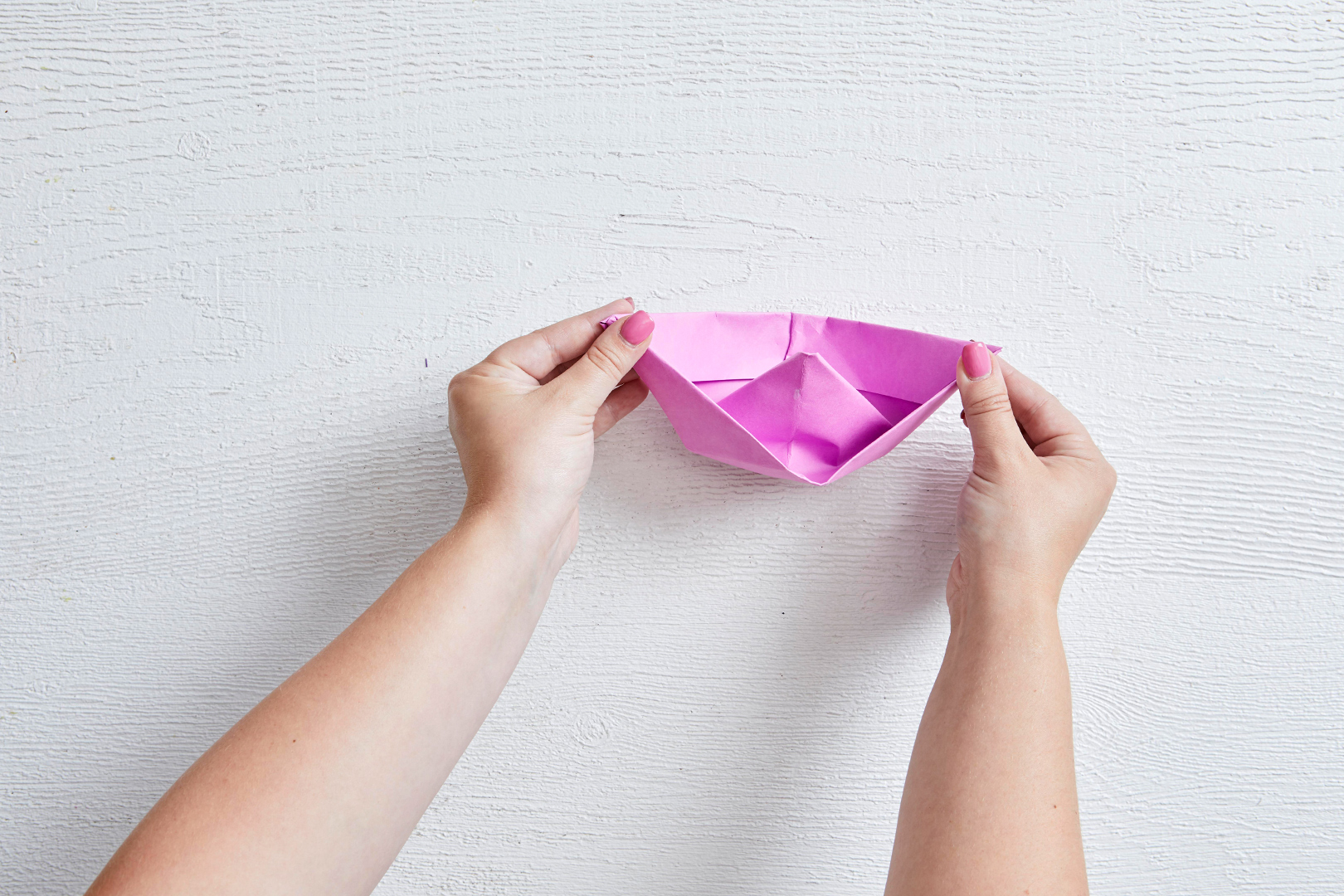 finished folded pink paper boat for appetizers