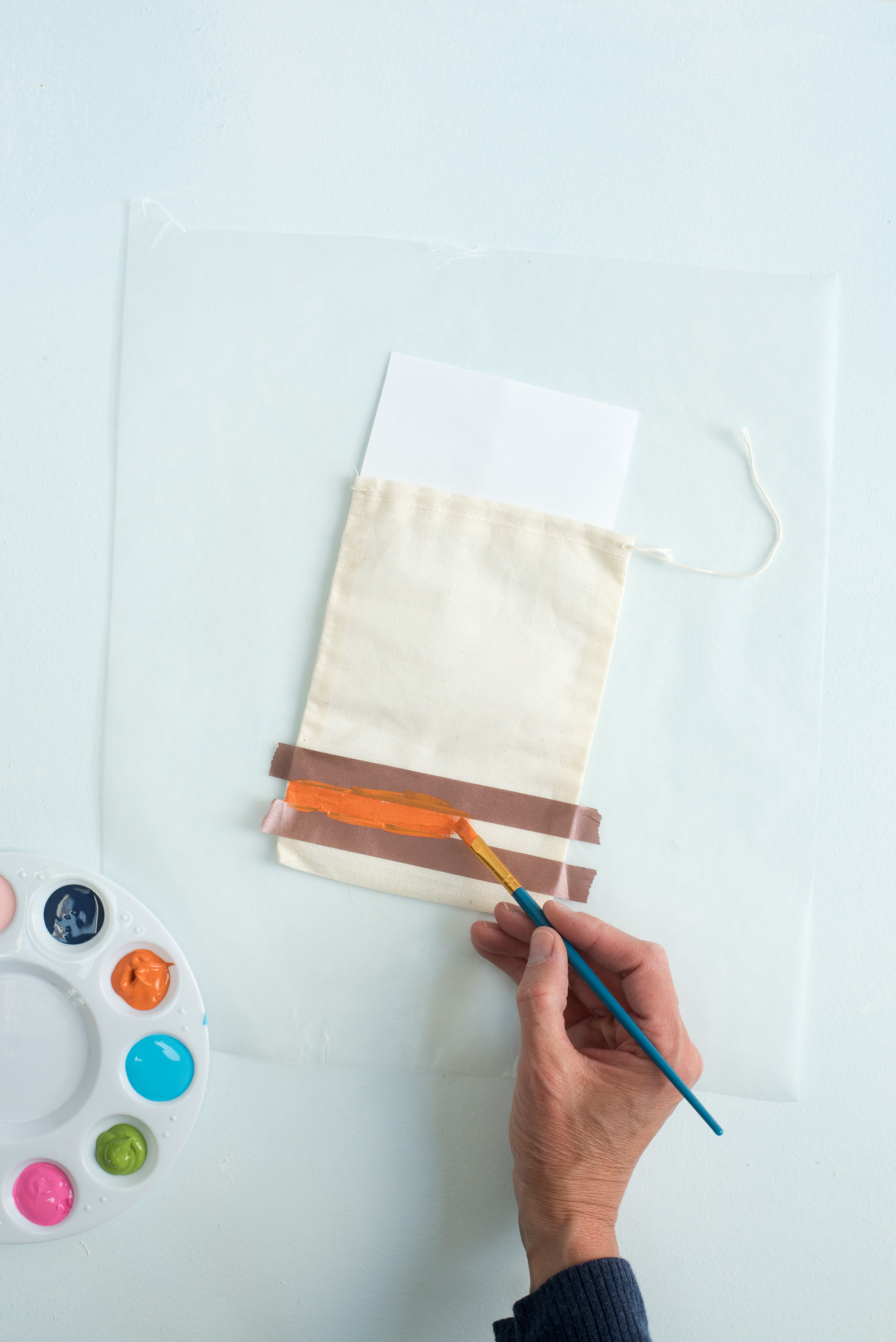 applying orange paint between tape for color detail busy bag