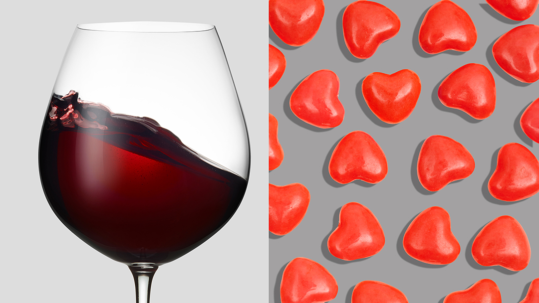 glass of malbec wine and graphic-looking cinnamon heart candies. Wine and candy pairing