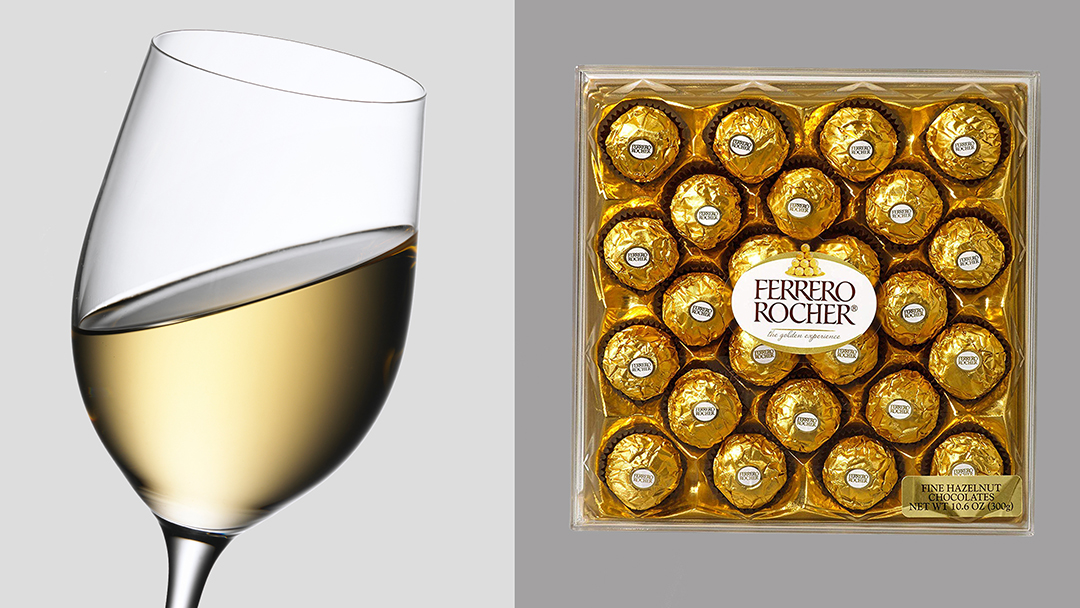 Glass of chardonnay and box of Ferrero Rocher candies. Wine and candy pairing