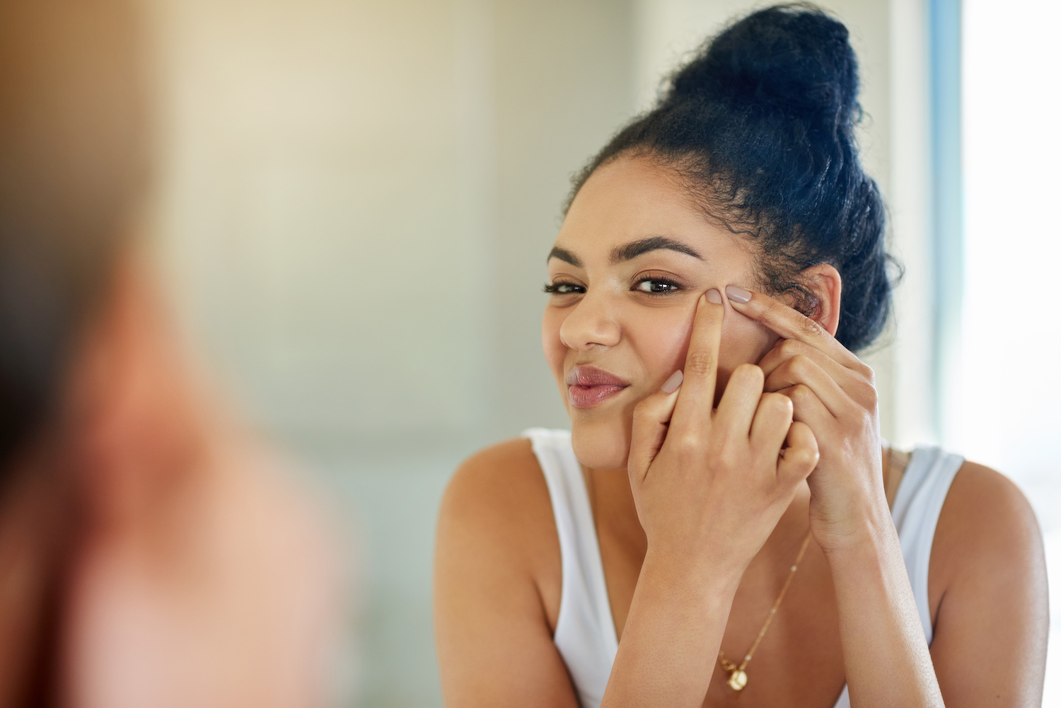 Young woman popping zit on face while looking in mirror