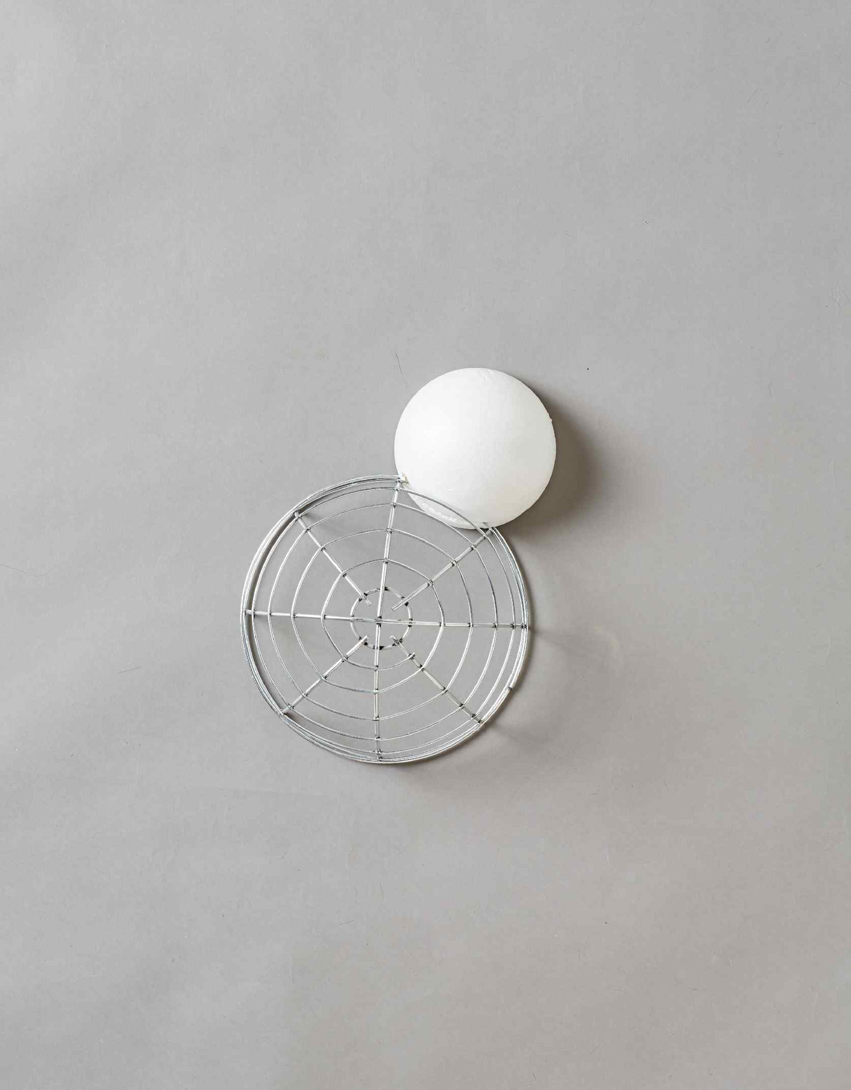 Small white foam ball glued to the side of a large silver wire sphere