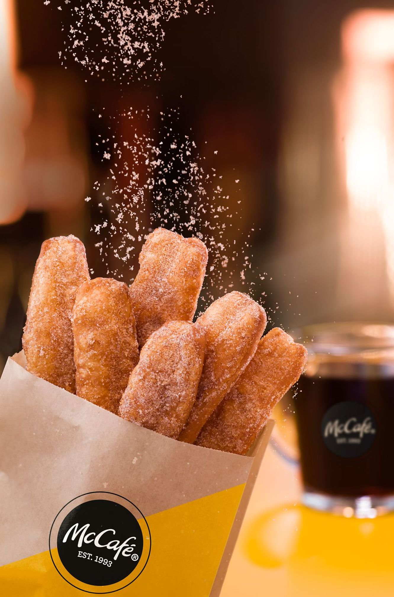 Six McDonald's Donut Sticks sticking out of a paper bag with cinnamon sugar being sprinkled on top