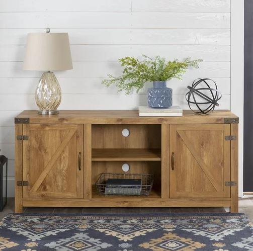 Farmhouse-style TV stand with natural wood finish, two cabinet doors on either end, open shelving in the center
