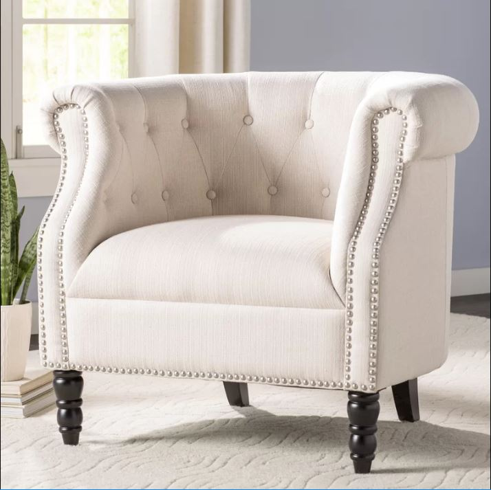 Off-white barrel-shaped armchair with tufted back and nailhead detailing around arm rests
