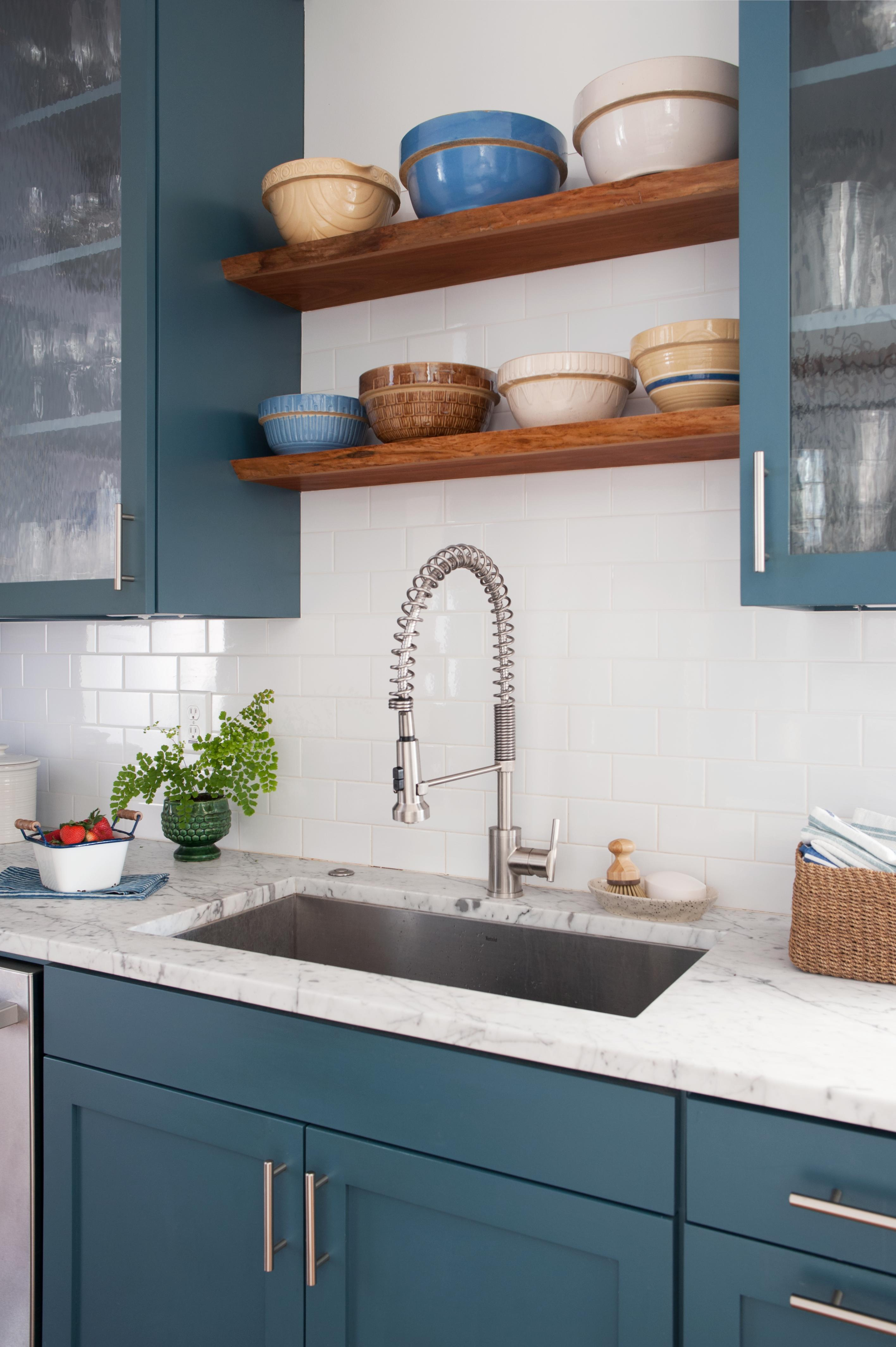 marble counter kitchen sink with blue cabinets and decorative bowls on wood shelves
