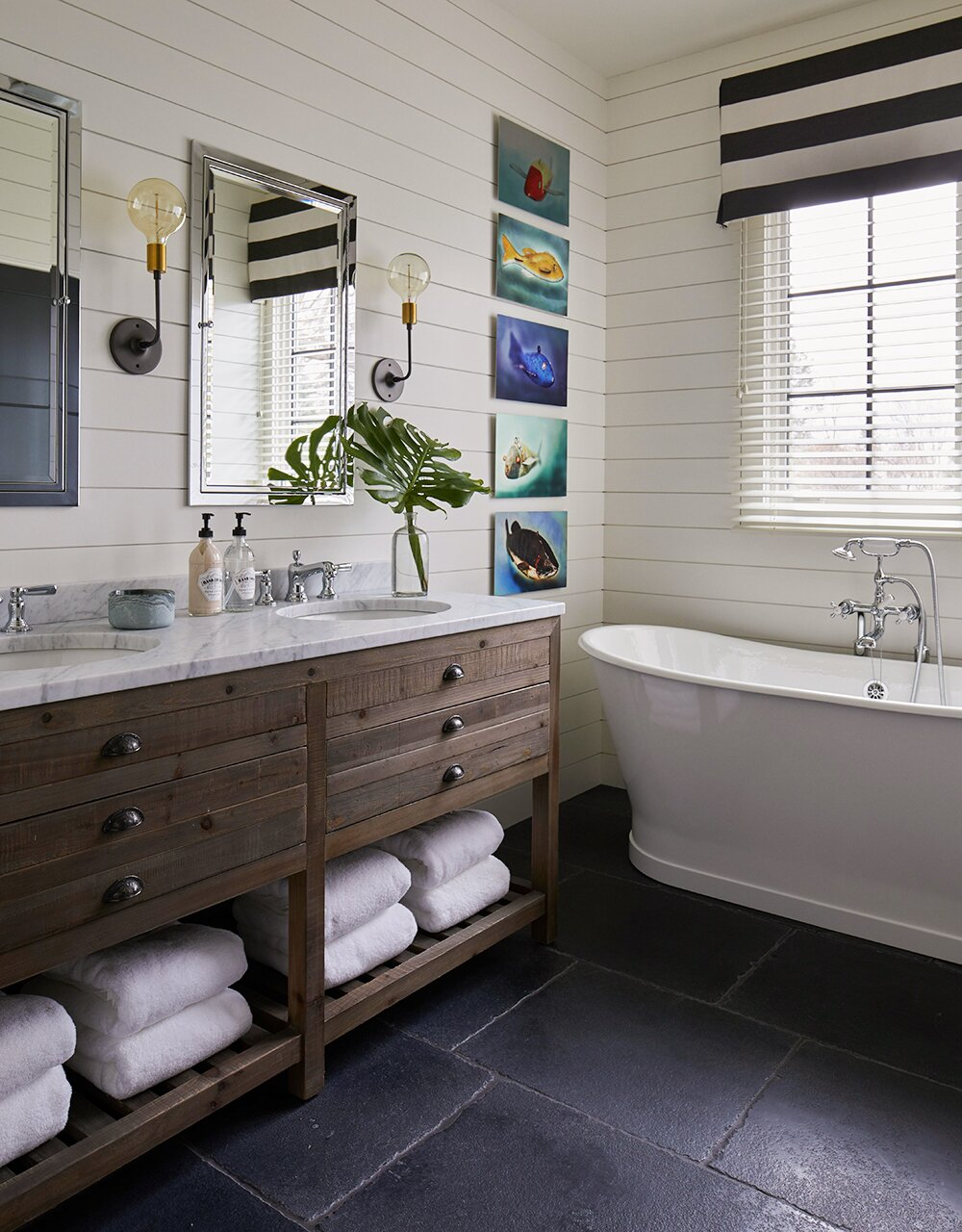 master bathroom with dual sink and white tub plus black tile flooring