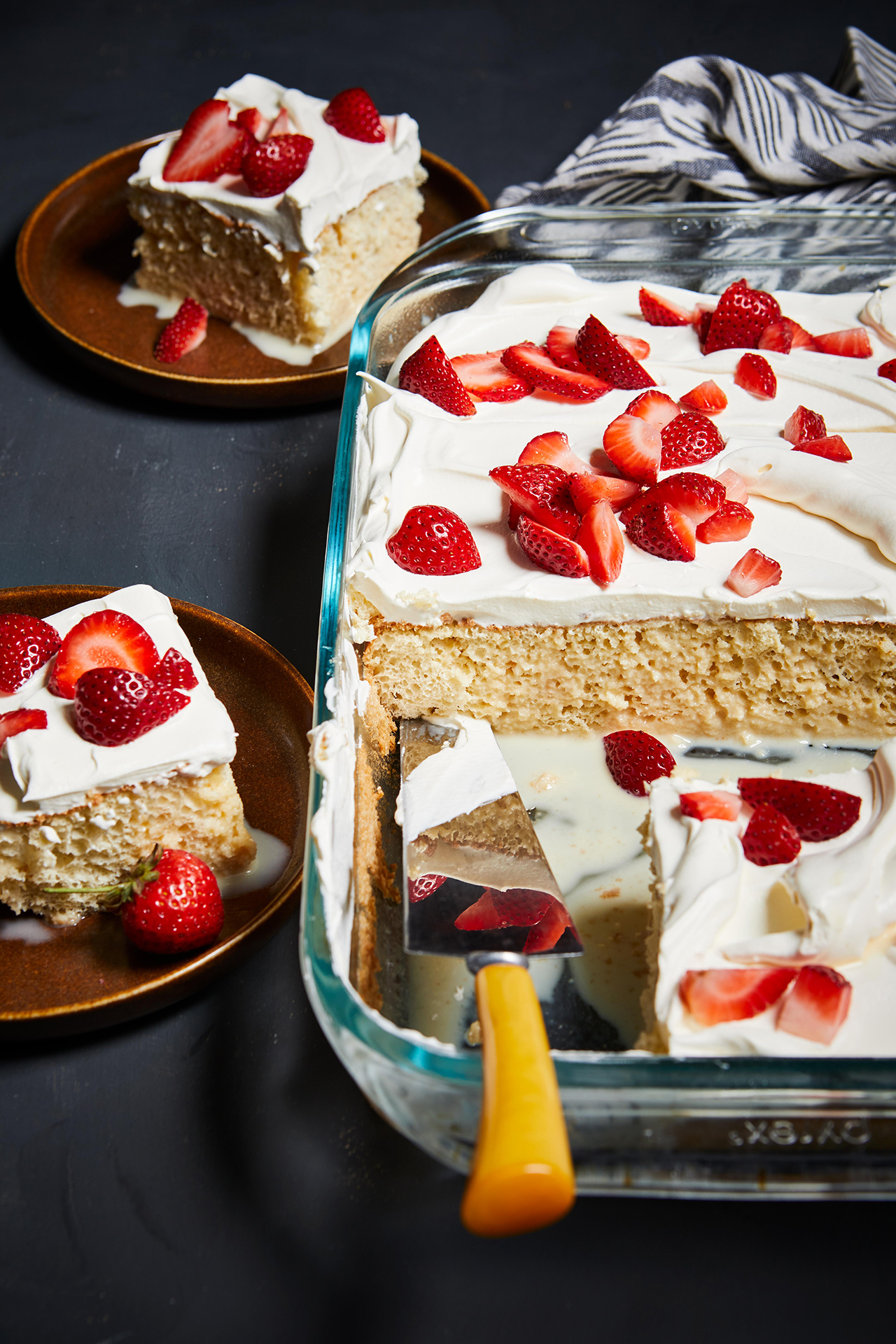 Homemade Tres Leches Cake with spatula in glass dish
