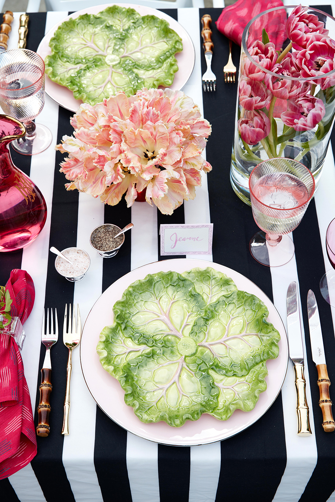 place setting with glass lettuce plate and tulips on striped table