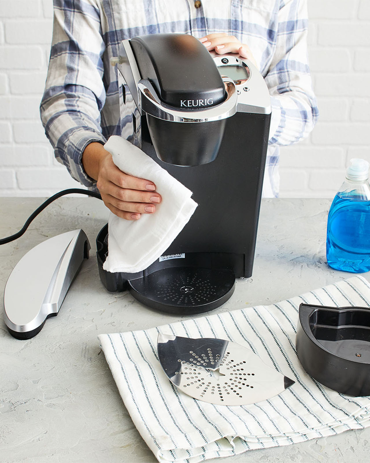 woman wearing plaid wiping down keurig with white towel