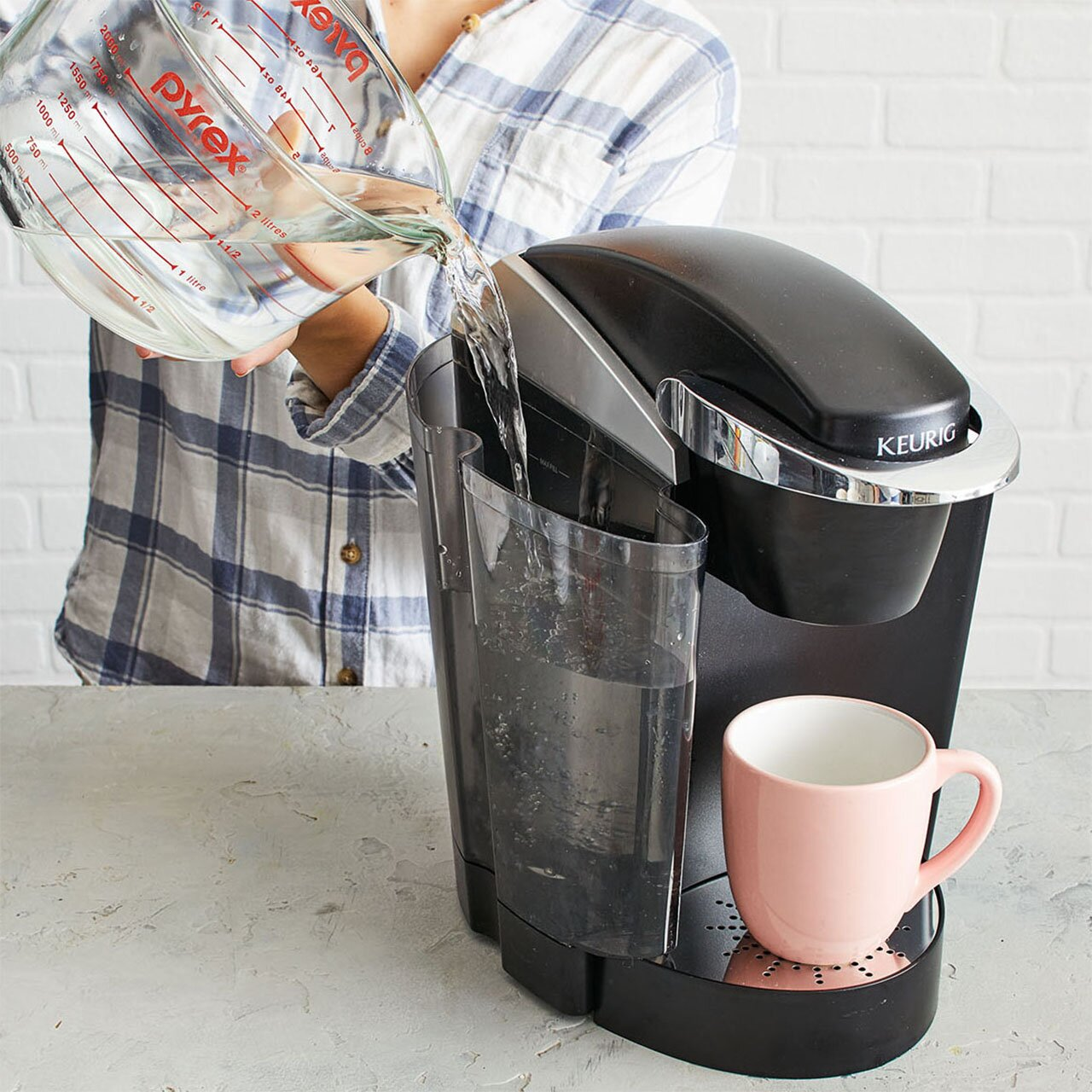 woman wearing plaid pouring water from pyrex measuring glass into keurig