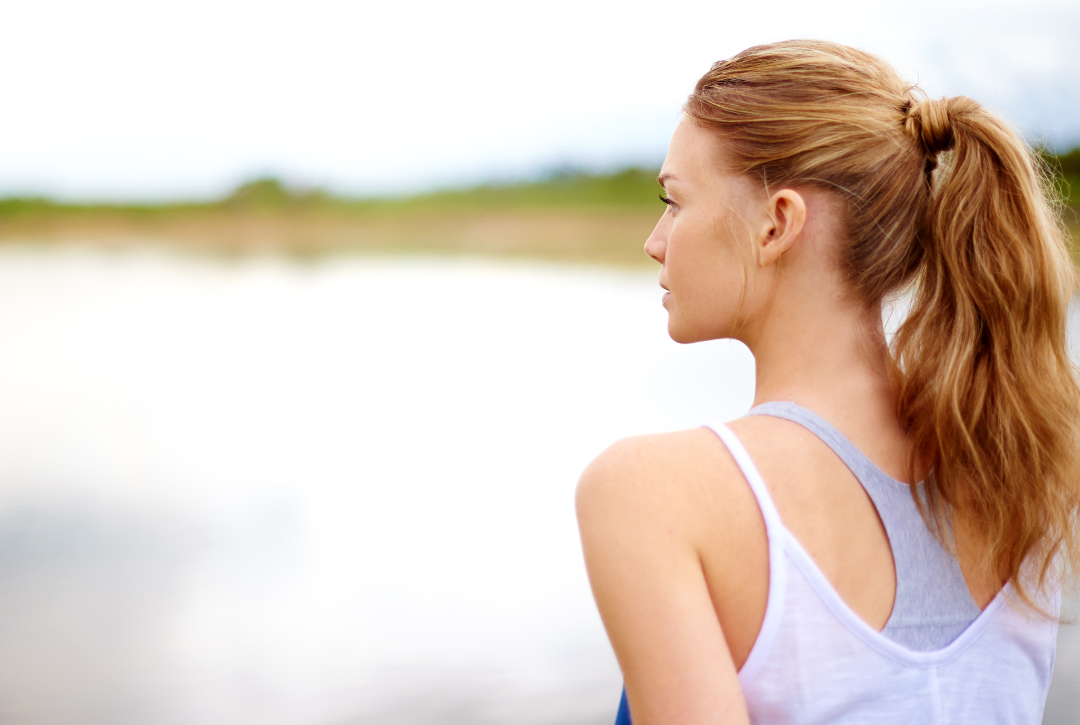 Rearview shot of woman with full ponytail looking out over a body of water