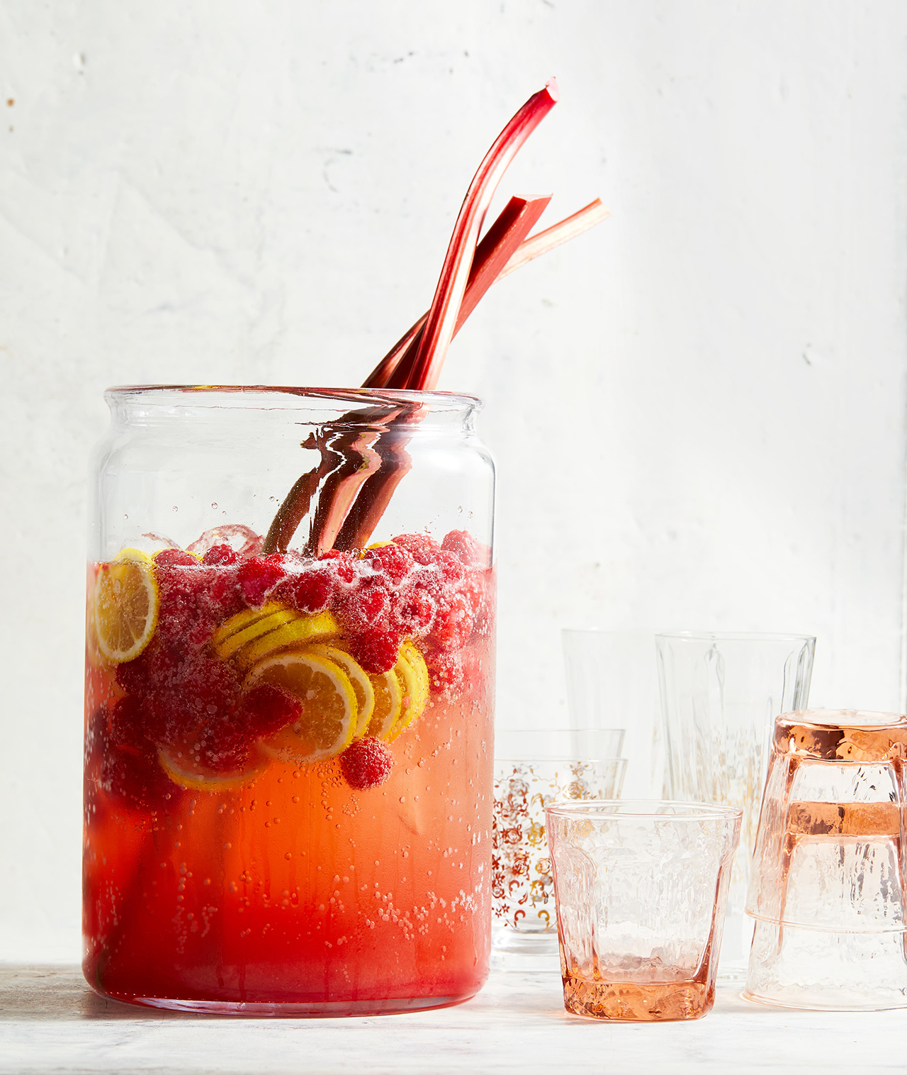 Ginger Rhubarb-Raspberry Punch in tall glass pitcher with drinking cups