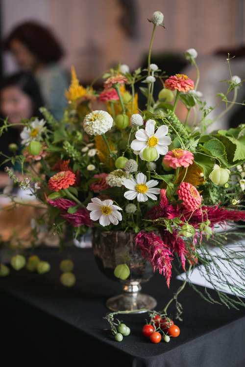Bouquet of cosmos, globe thistle, celosia and Chinese lantern plants in silver urn