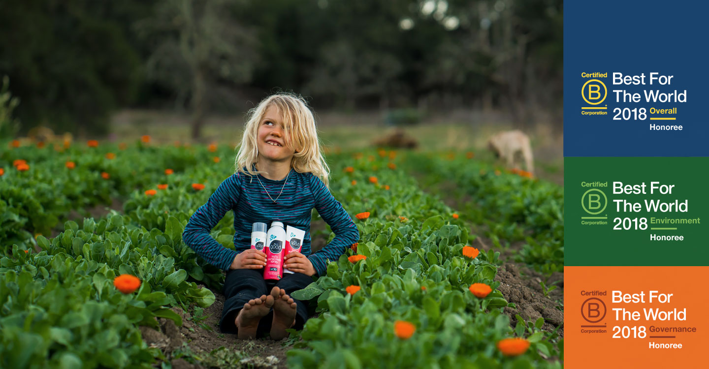 young kid with blonde hair sitting in a garden