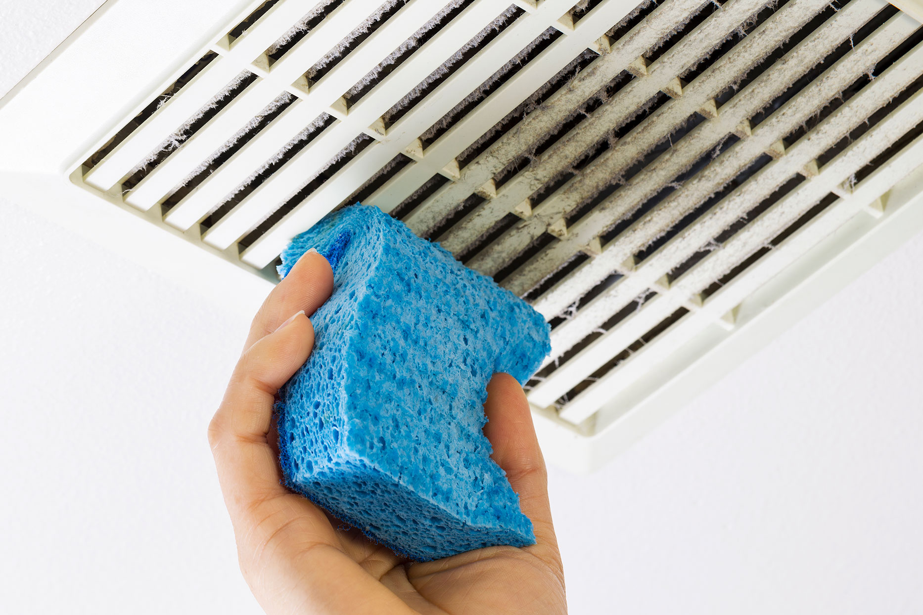cleaning bathroom fan with sponge