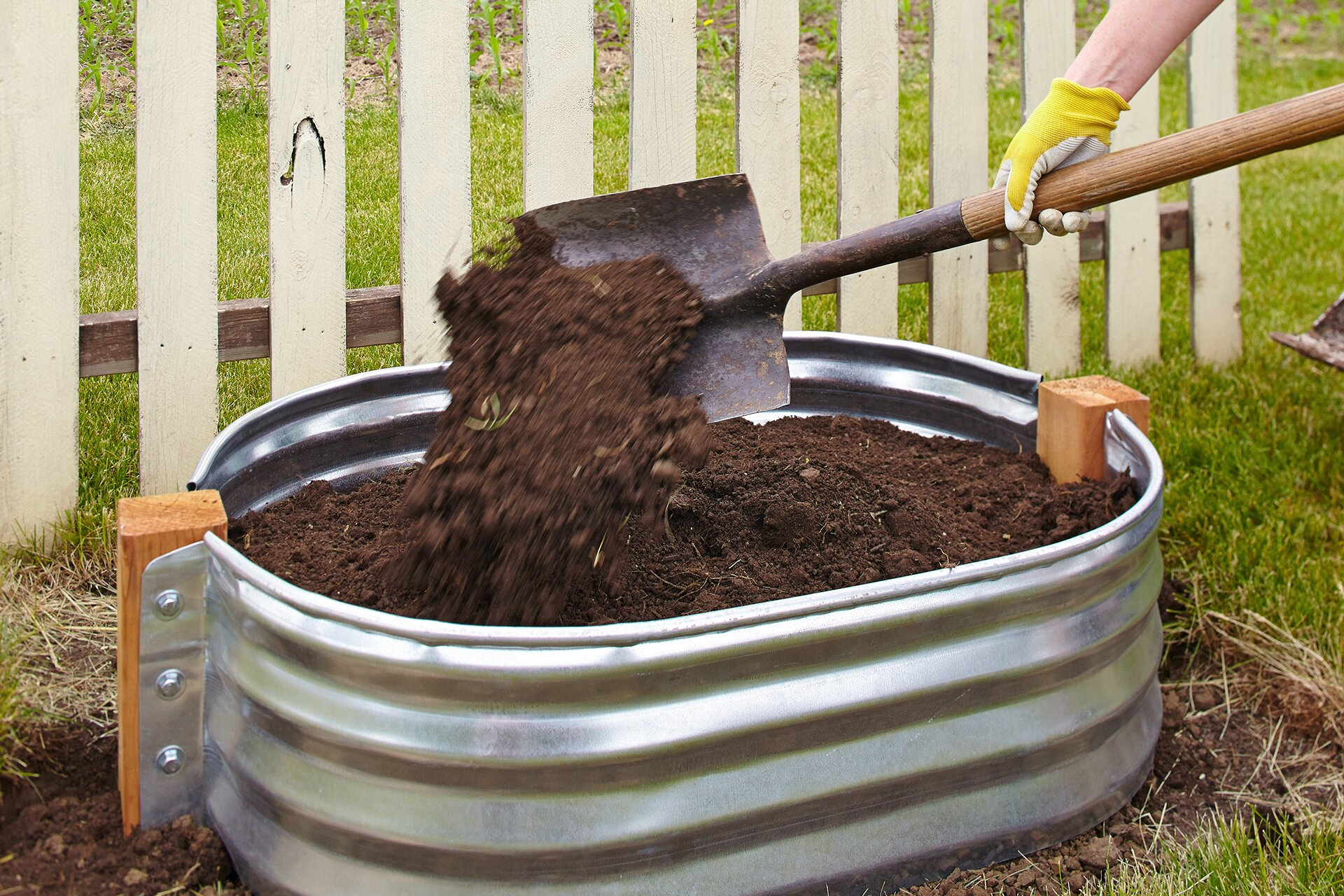 adding soil to metal tub with garden shovel