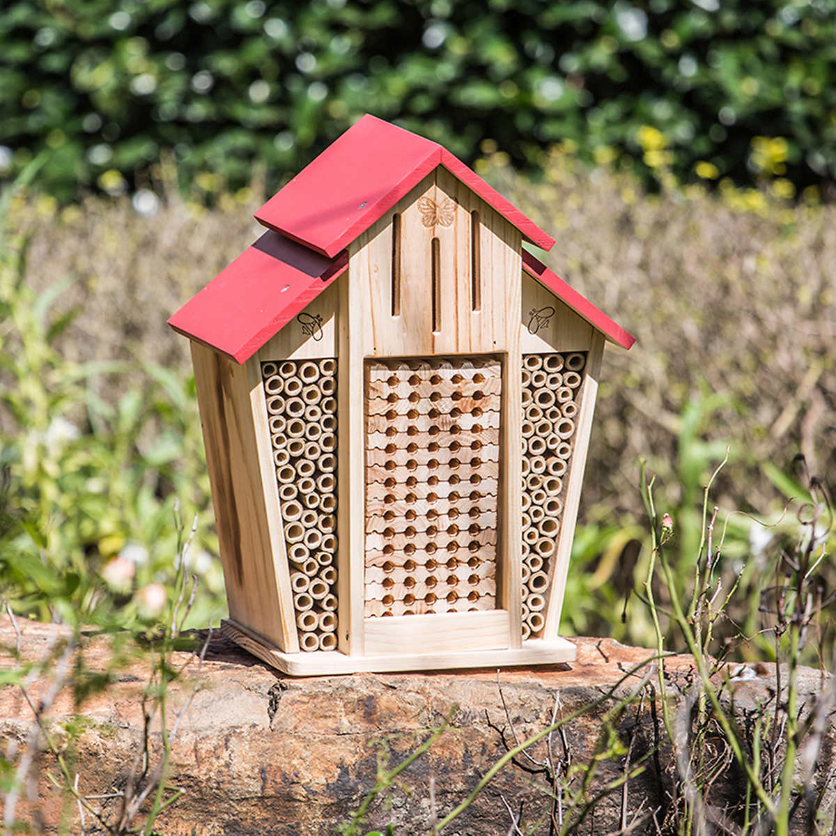 Pine house-shaped mason bee barn with bamboo nesting tubes and red painted roof and monarch shelter slats on top