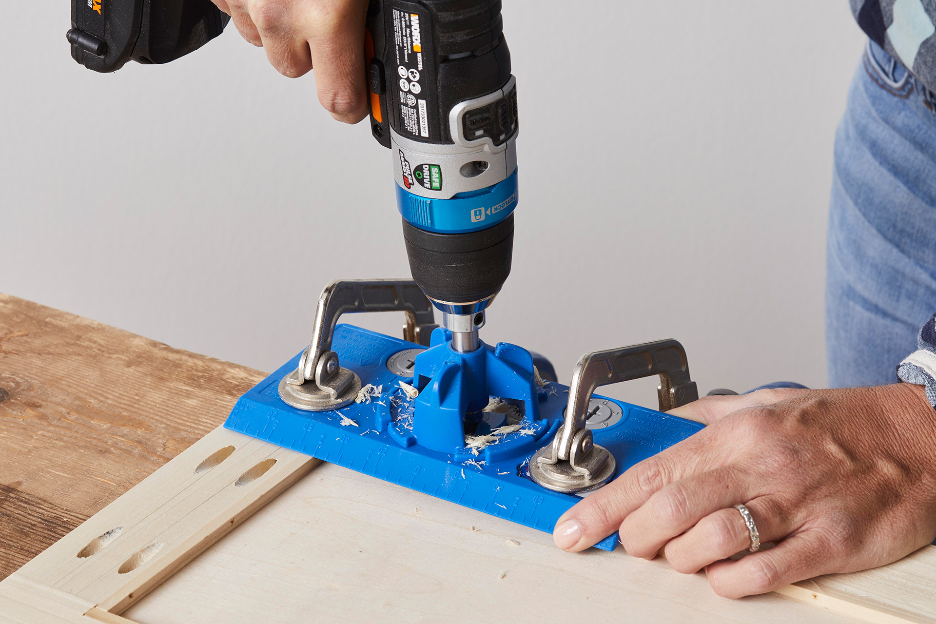 man holding electric drill and clamp for wood cabinet project