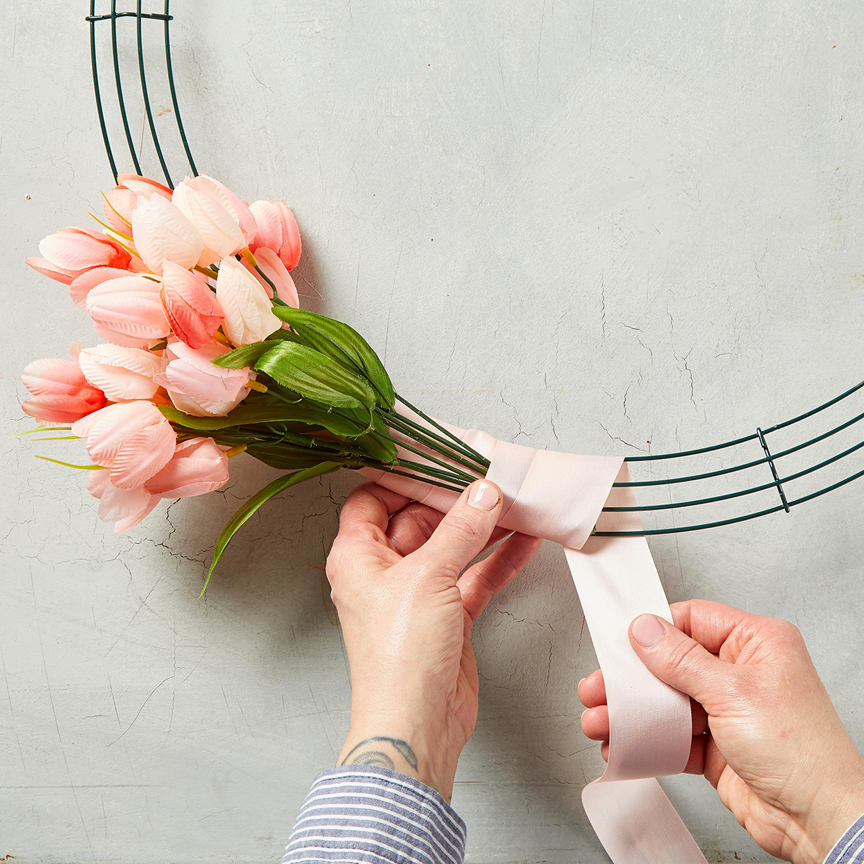 placing bunch of tulips and wrapping ribbon