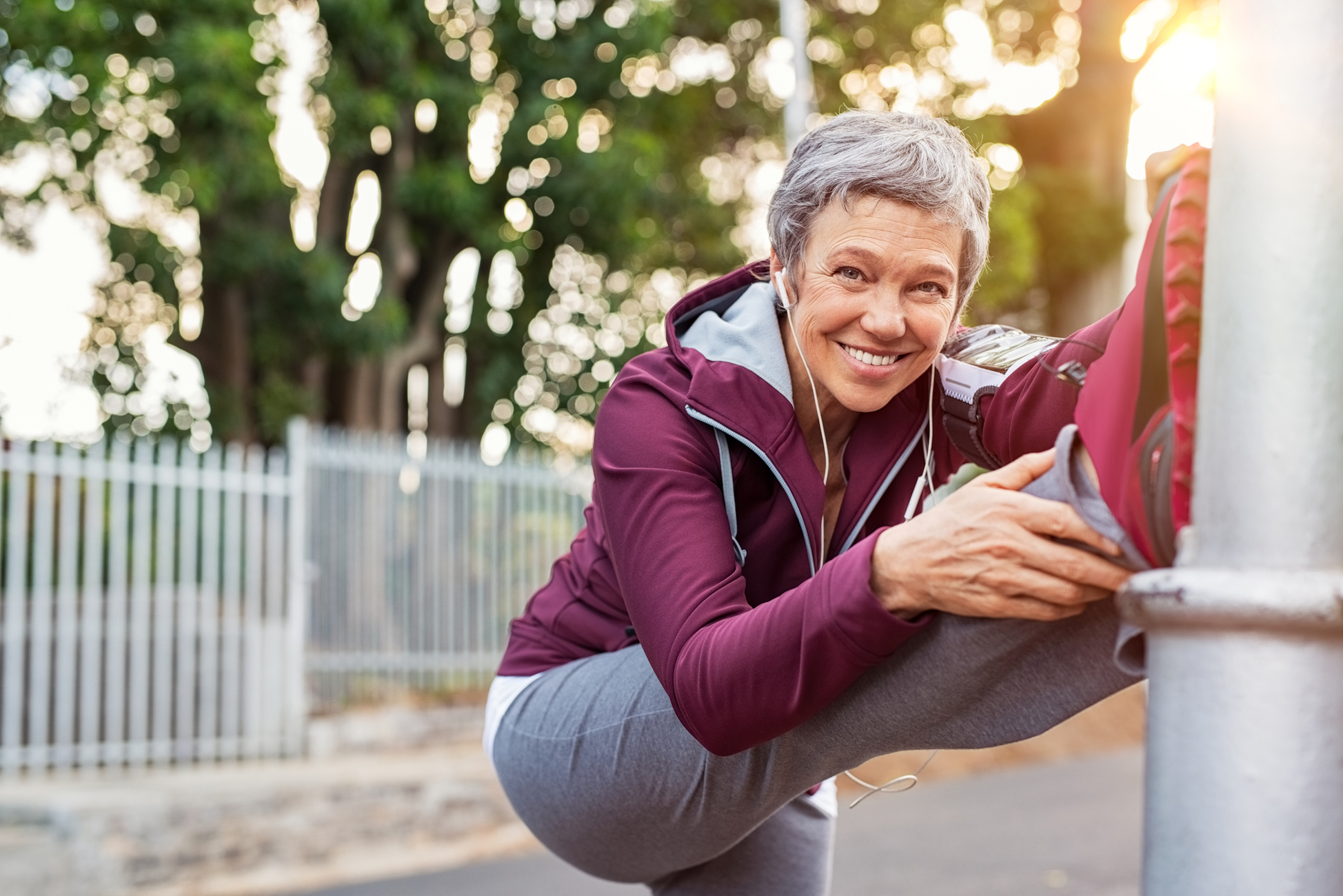 Smiling mature woman warming up before morning jog