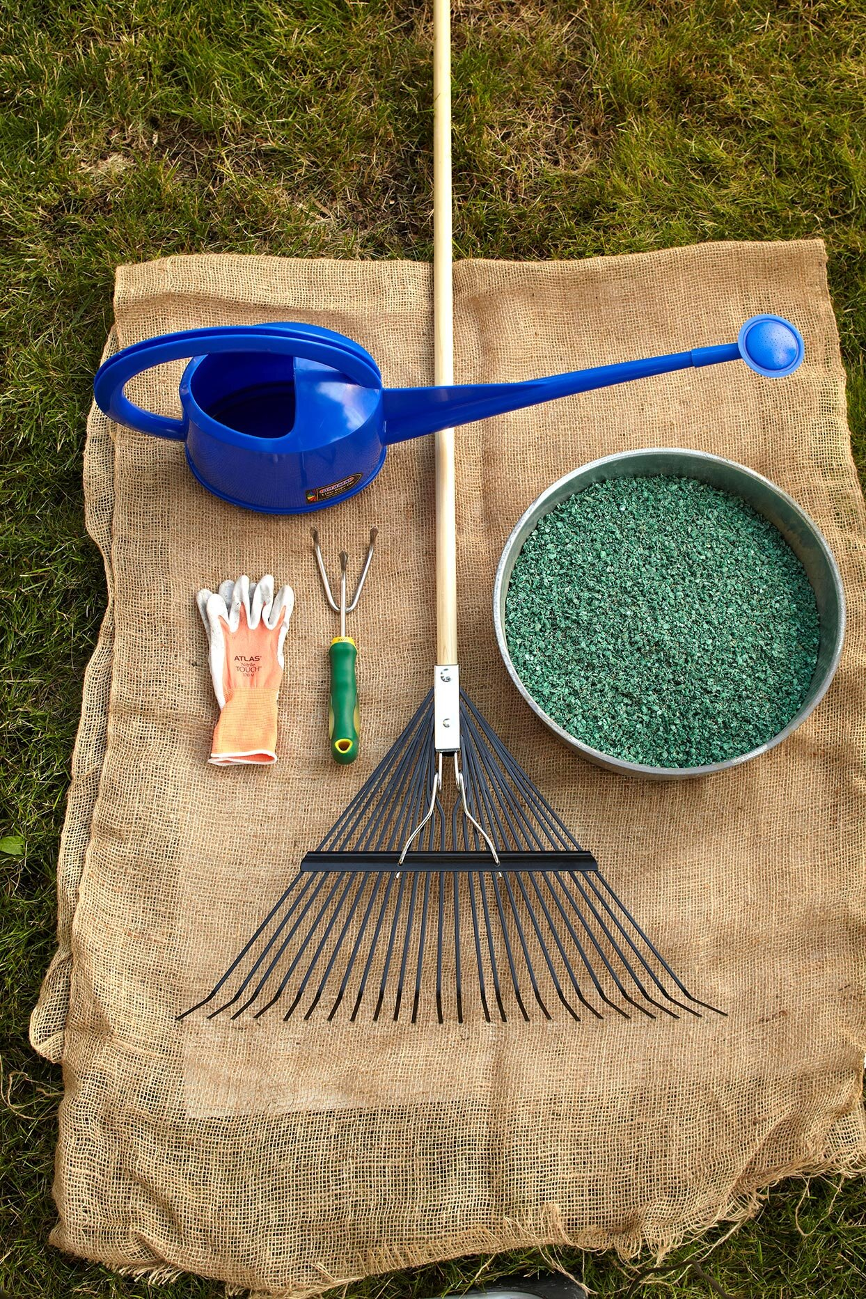 rake, gloves, fertilizer, and watering can tools