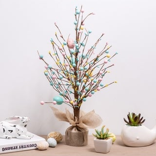 twig branch tree decorated with easter eggs, sitting on a side table