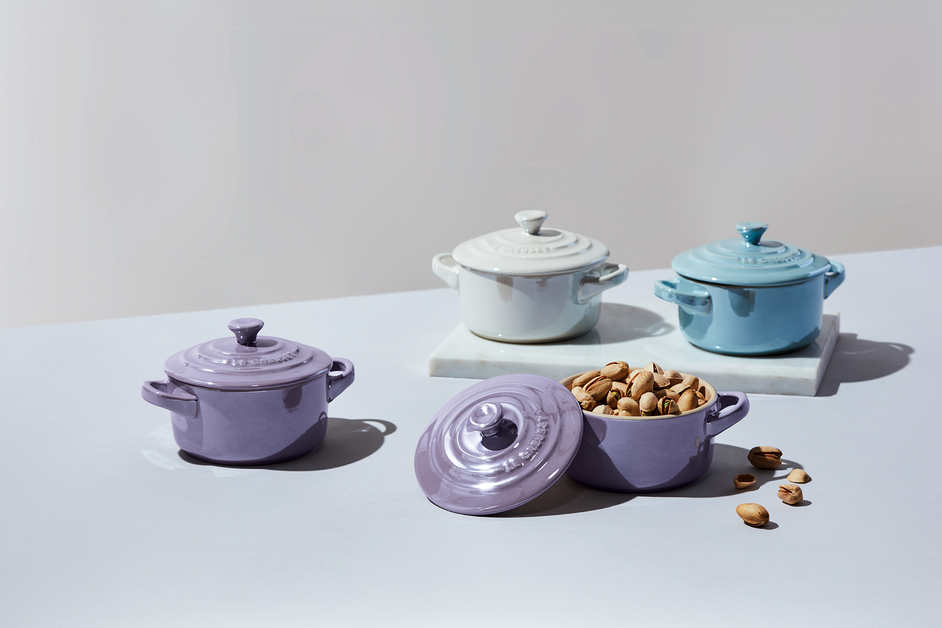 Le Creuset metallic mini cocottes in purple, blue, and white with nuts in purple cocotte