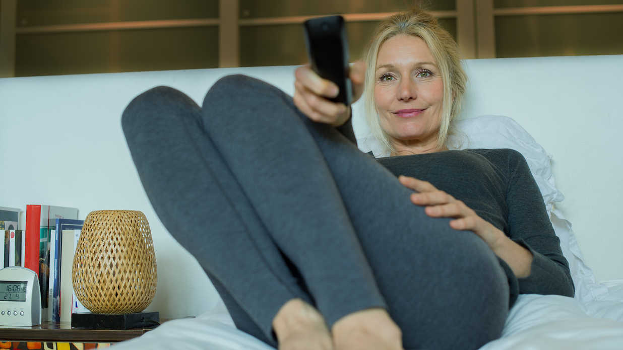 woman with blond hair hold a TV remote while sitting in bed