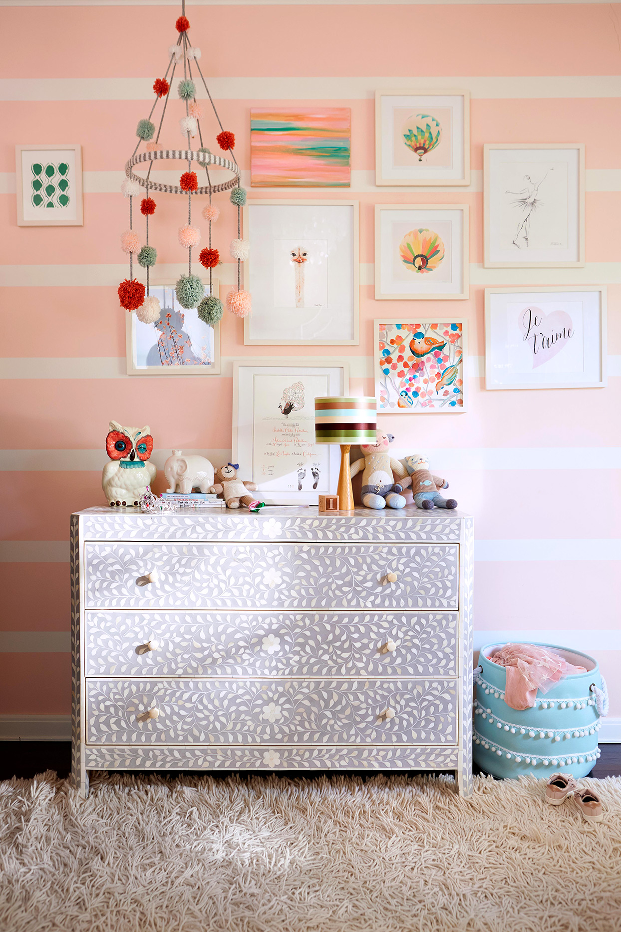girls bedroom with painted dresser, framed artwork on wall and pink striped walls