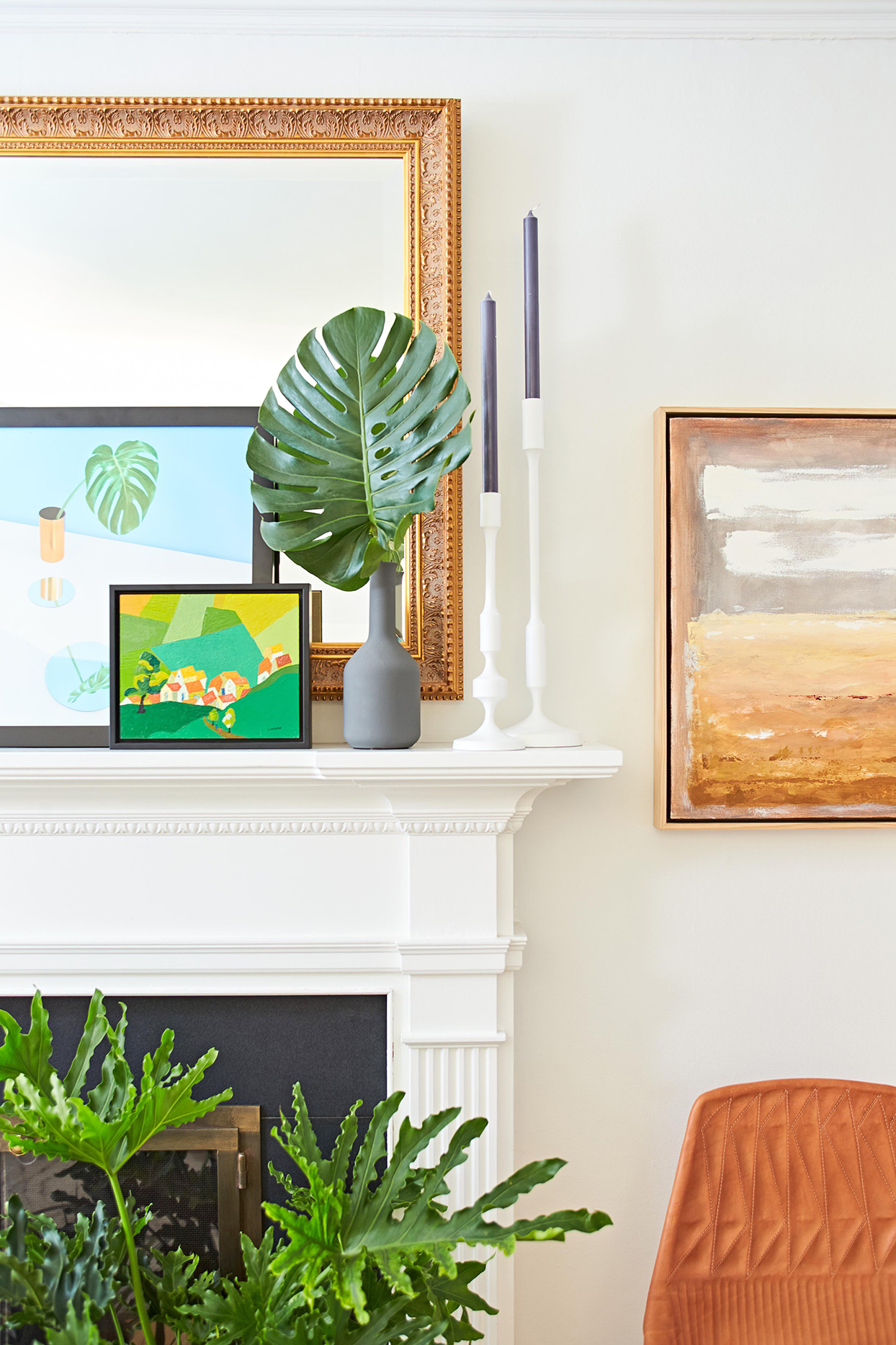 detail shot of white fireplace with prints, gold-edged mirror, white candlesticks with blue tapers; and gray vase with large frond