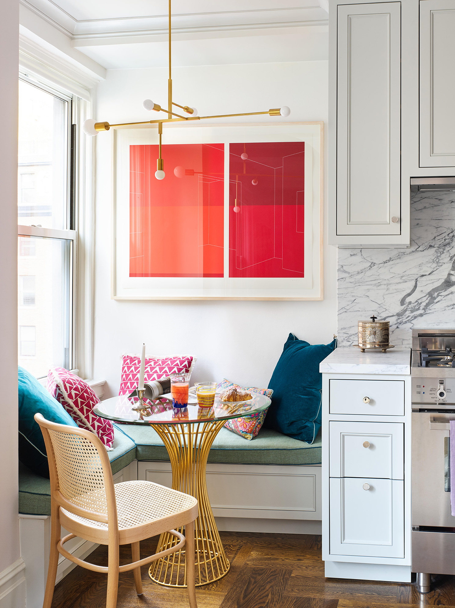 kitchen banquette with bold artwork in reds