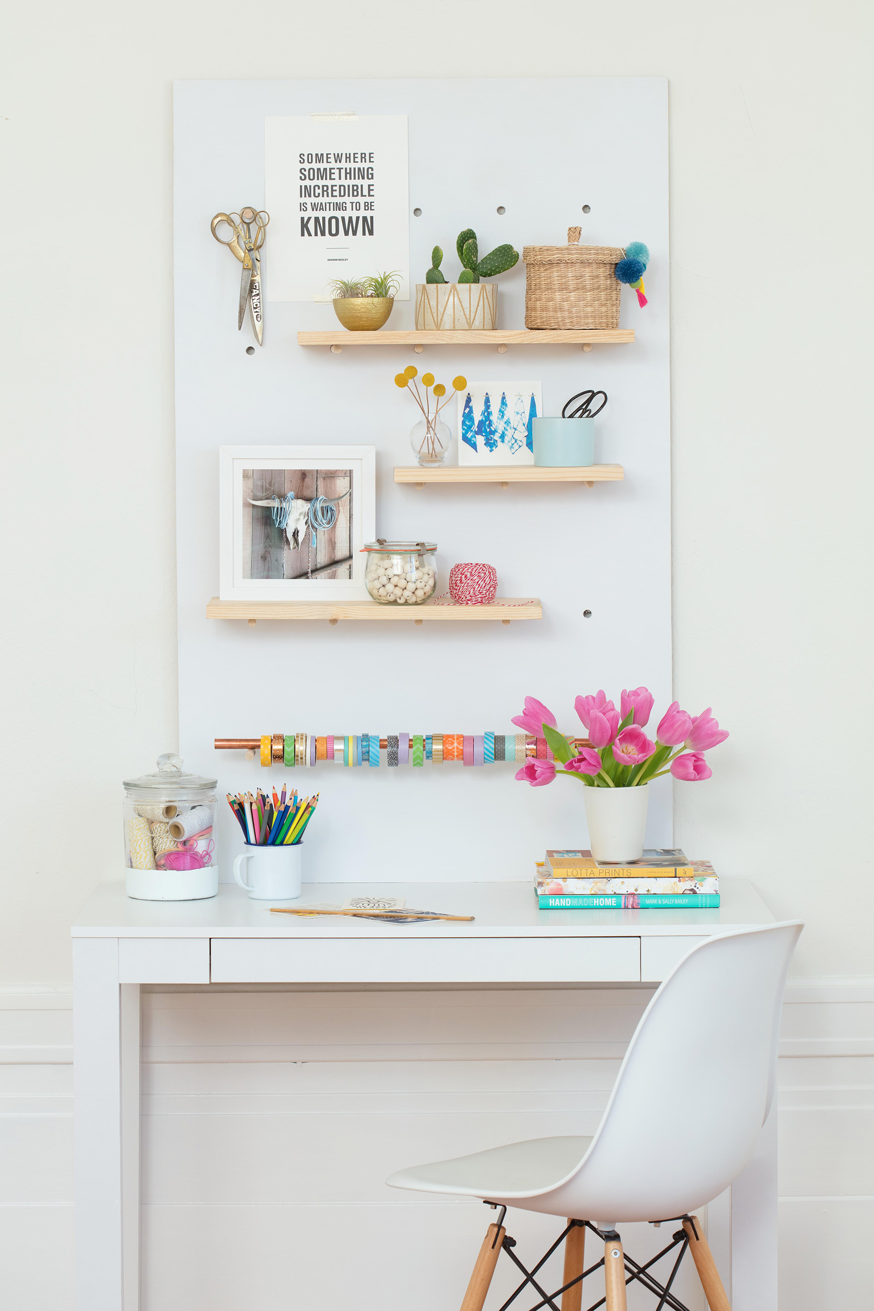 desk with white pegboard on wall with shelves