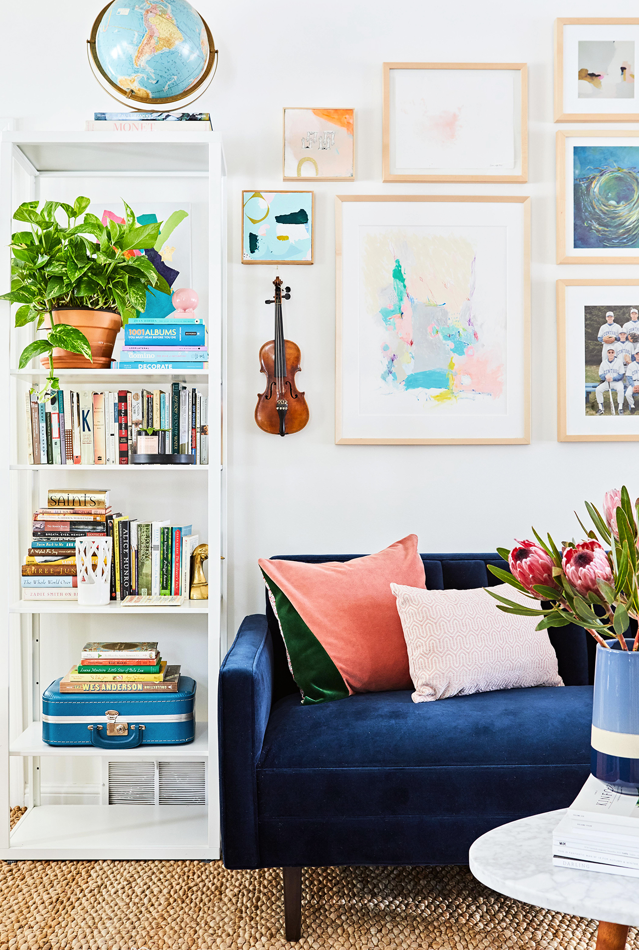white living room with colorful sofa white bookcase art books