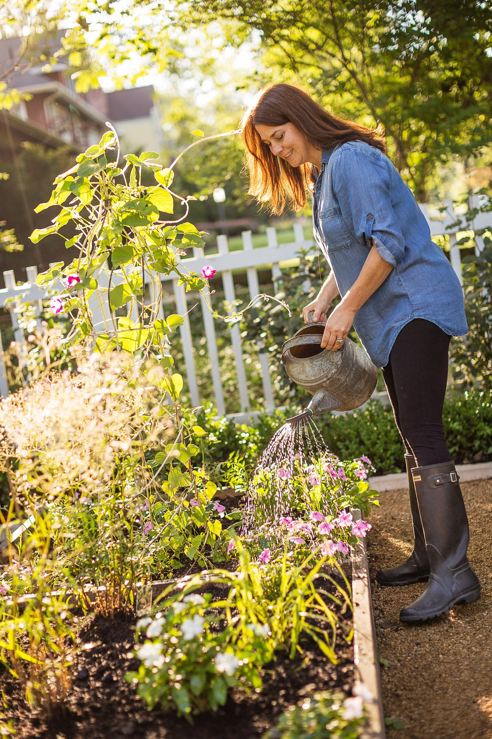 woman in rubber boots watering newly planted herbs