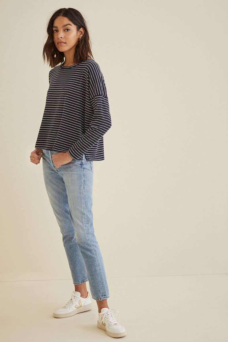 Amour Vert woman with medium skin tone and dark brown hair wearing light wash ankle cut jeans and loose, navy and white striped long sleeve tee