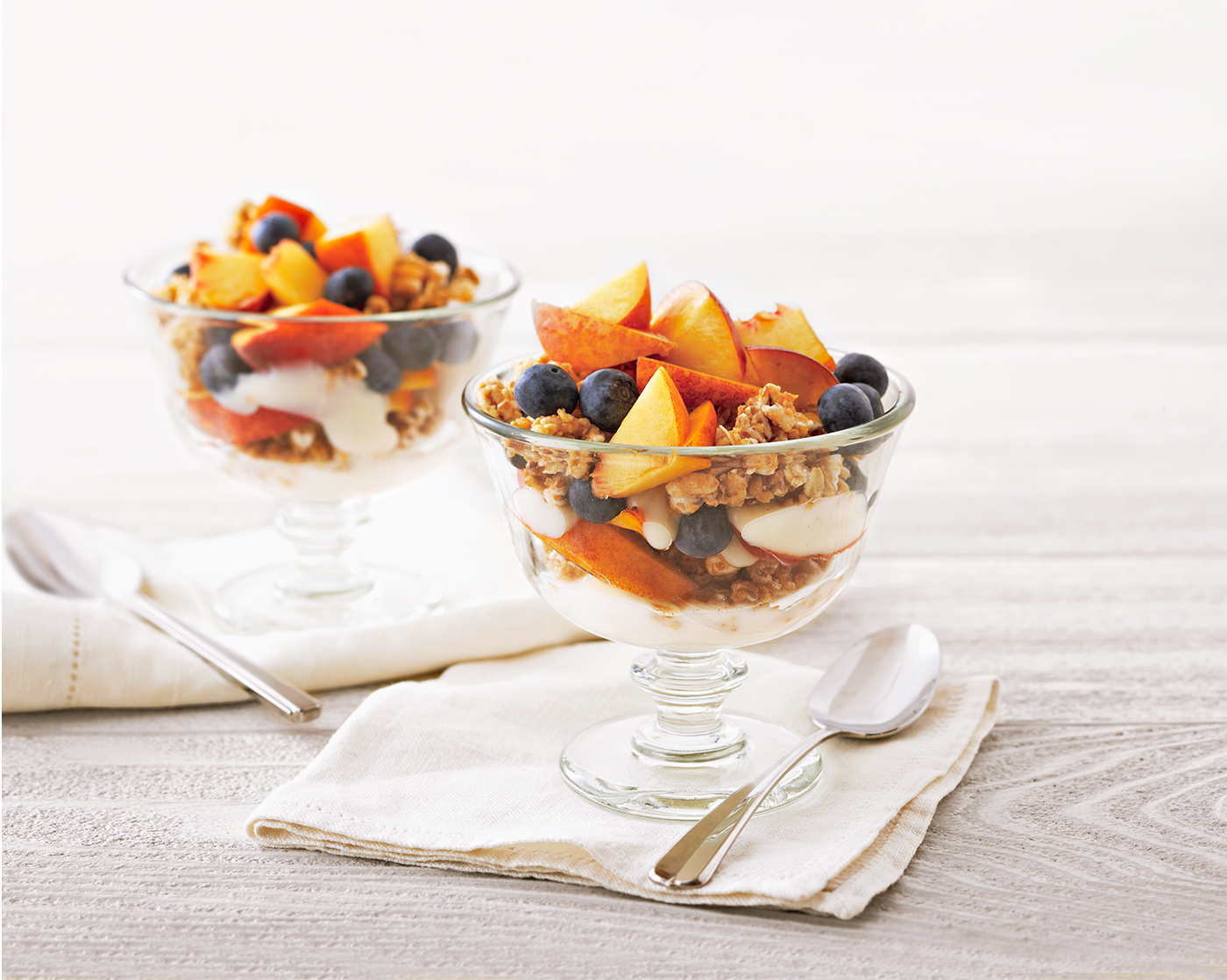 two clear glass dishes of Peach-Blueberry Parfait