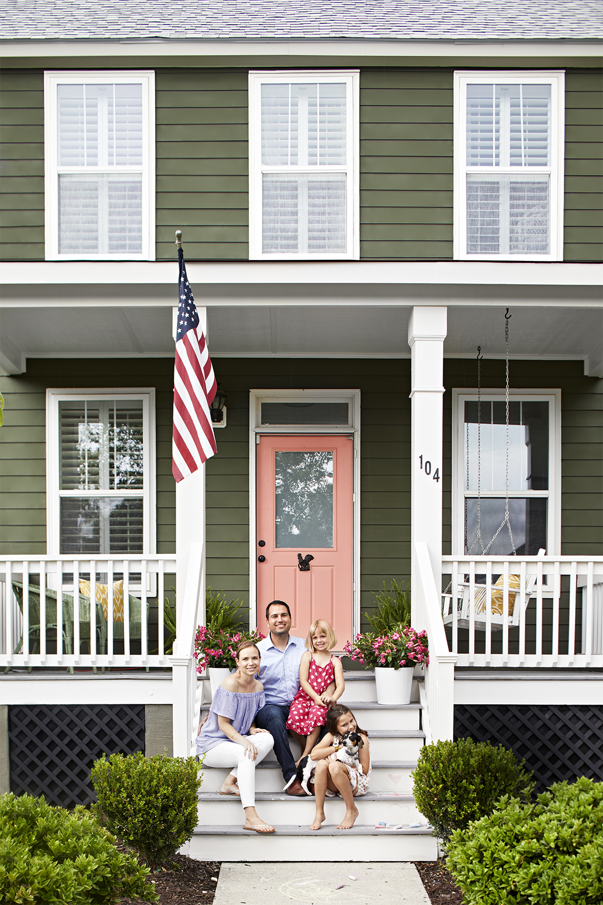 family sitting on front porch of green home