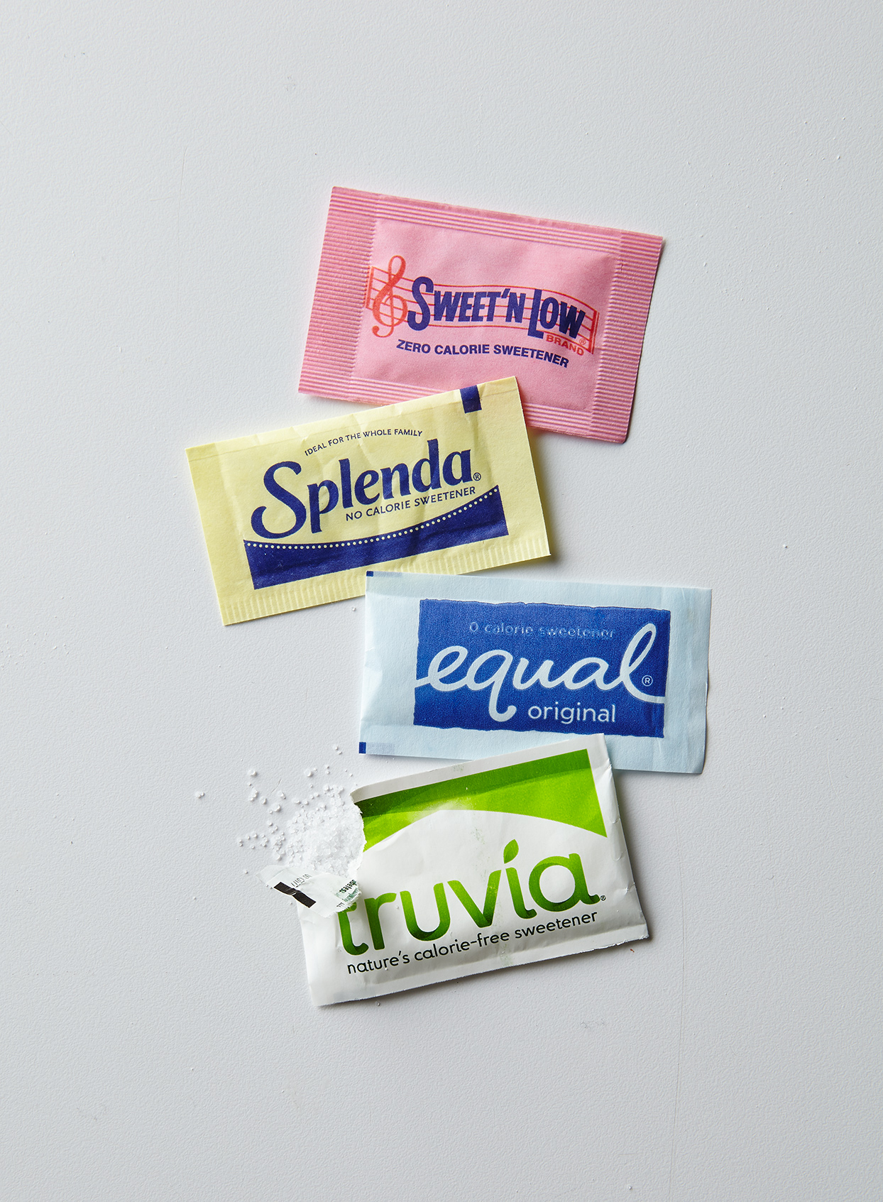 Sugar substitute packets including Equal, Truvia, and Splenda on white background