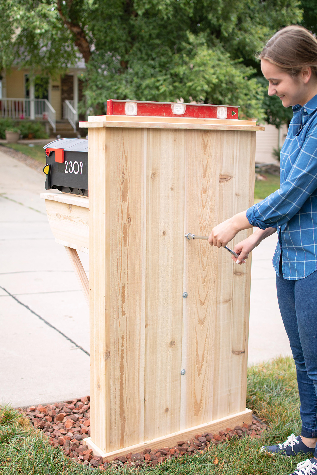 using tools to level wood mailbox structure
