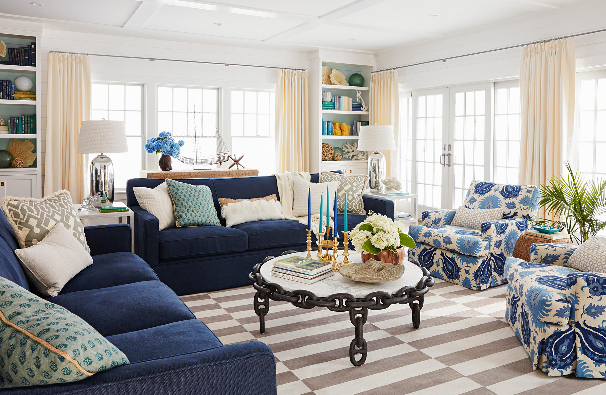 living room with blue furniture and ivory curtains