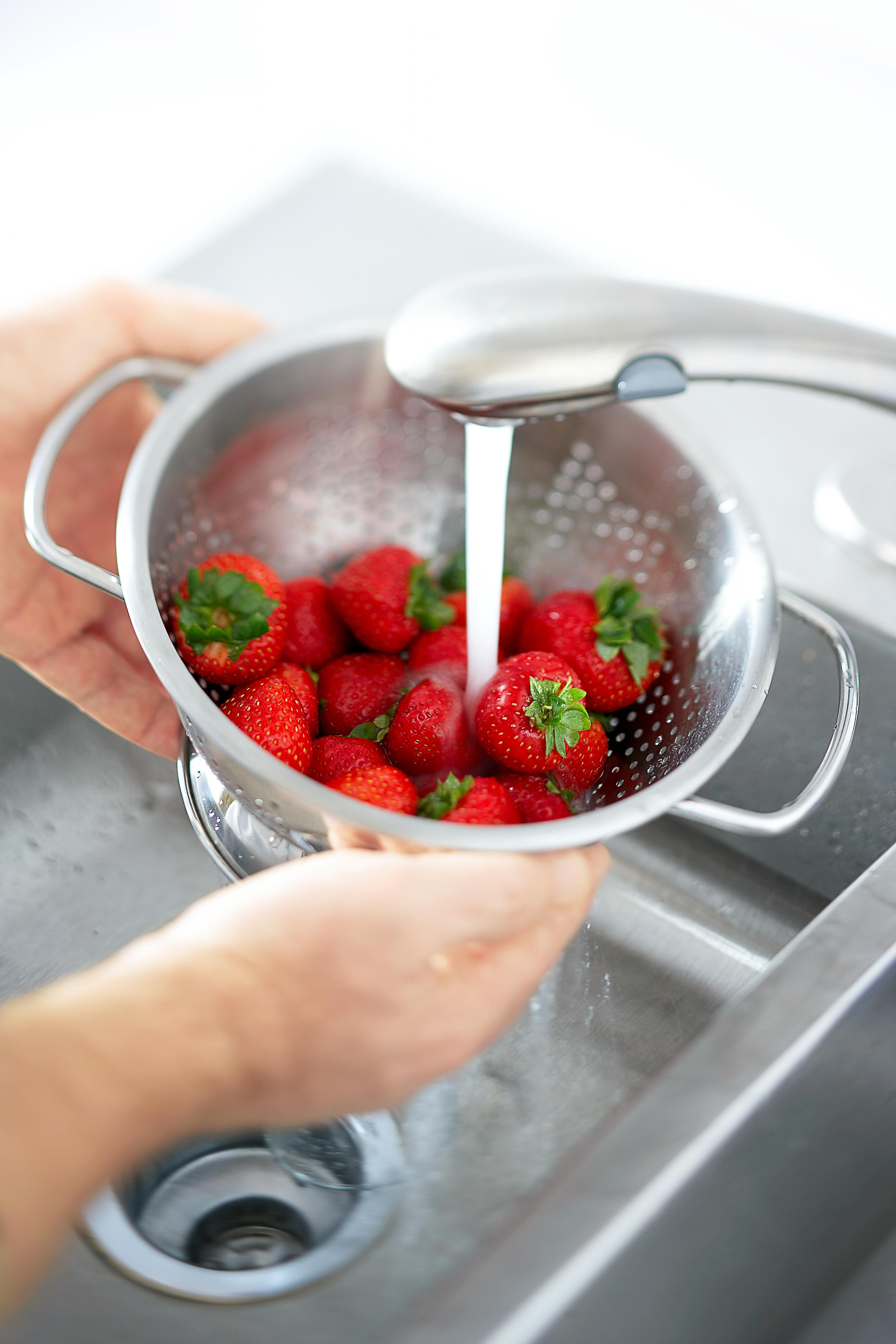 rinsing strawberries in colander under faucet