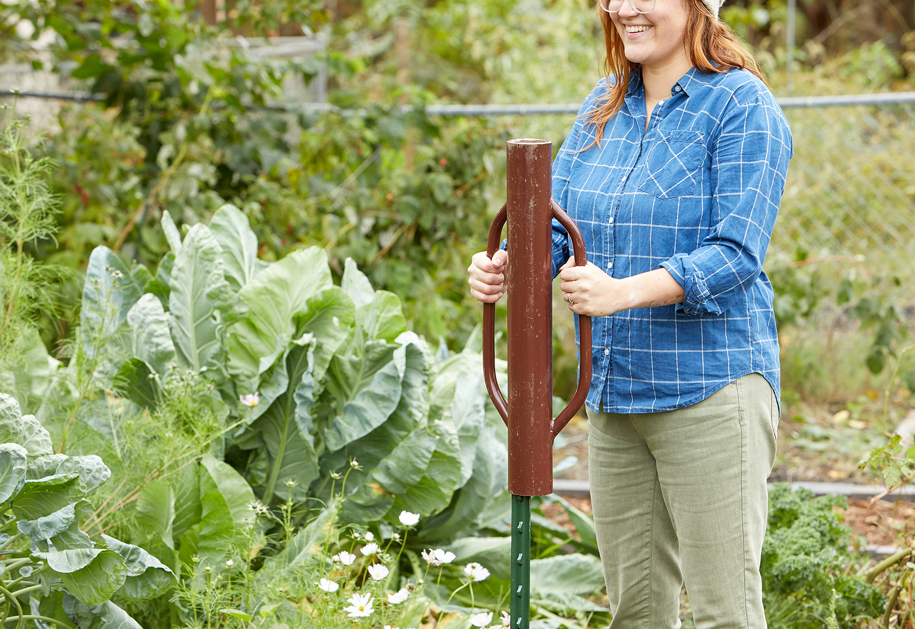woman using fence post driver in garden