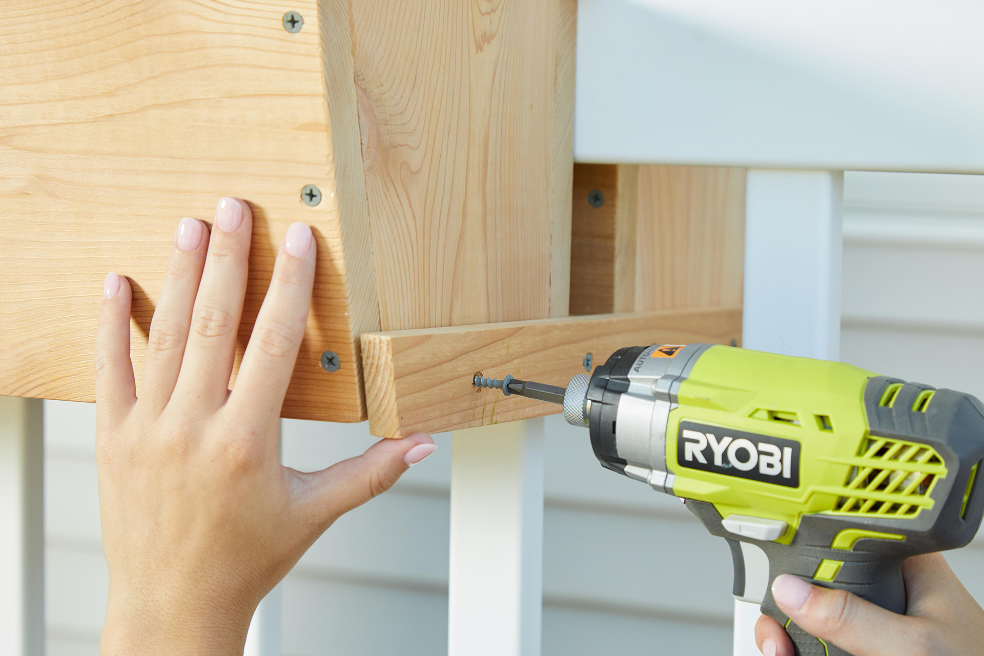 inserting screw with electric drill for wood box planter
