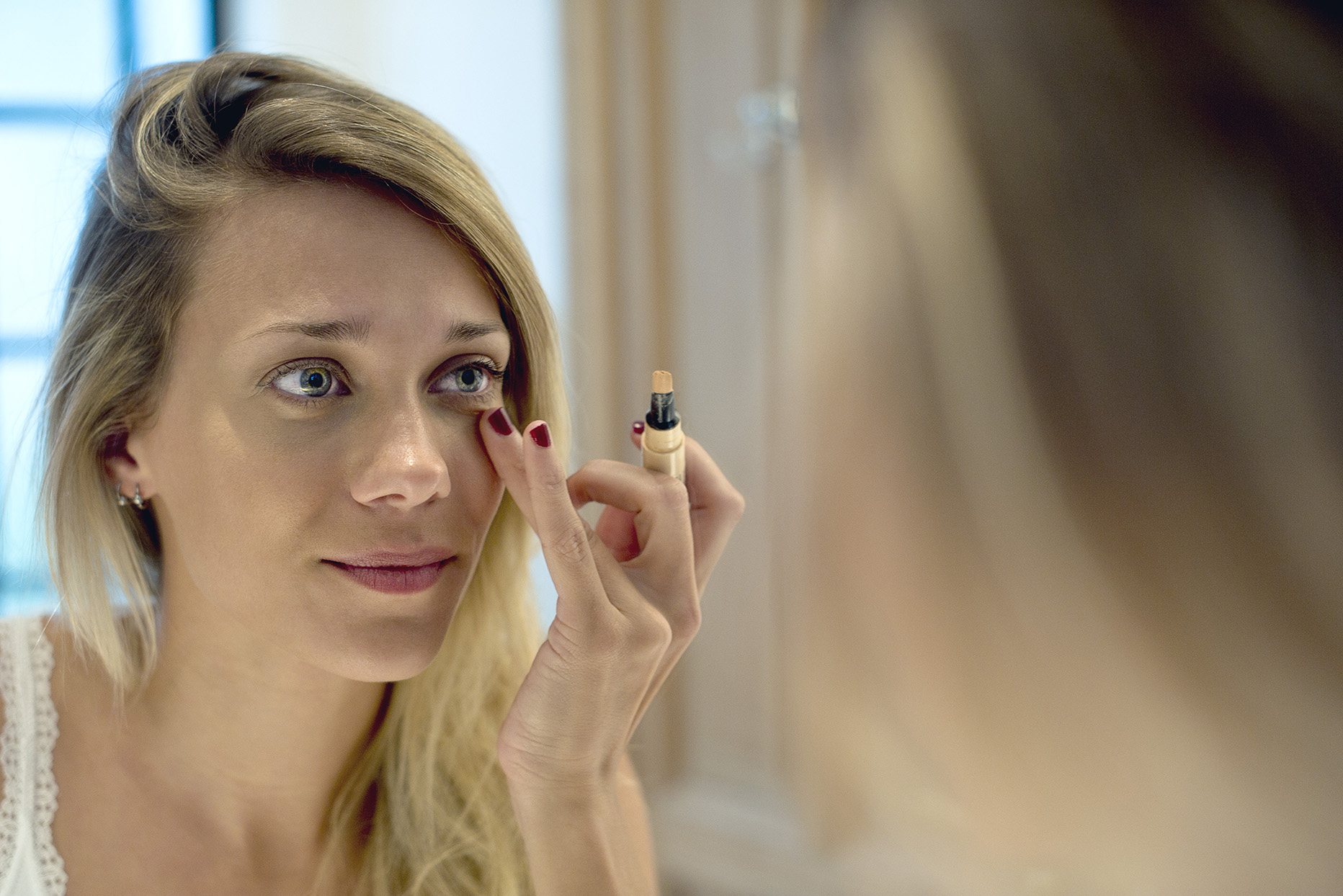 Blond woman applying concealer under eyes while looking in a mirror