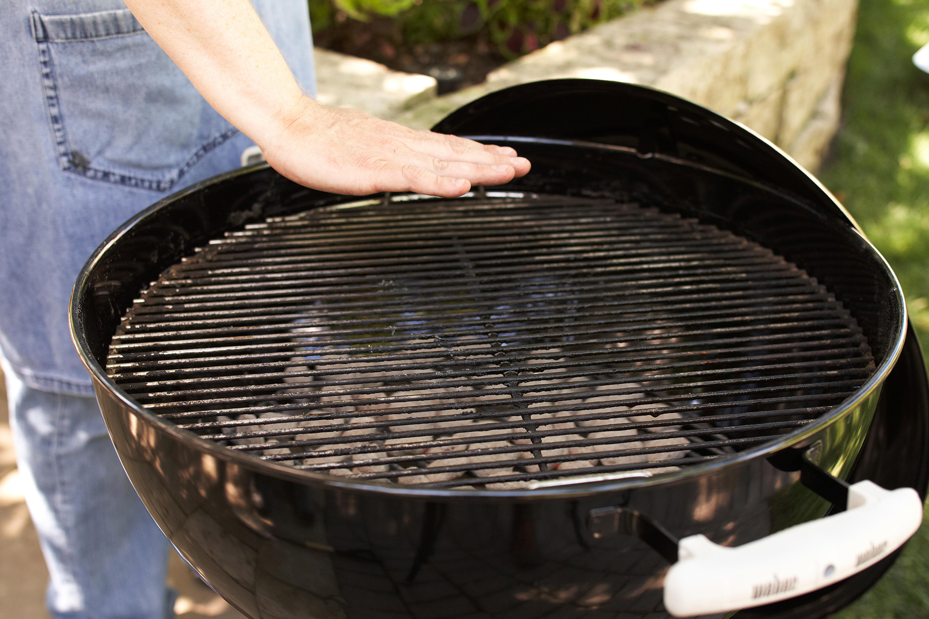Using the hand method to test grill temperature over a charcoal grill