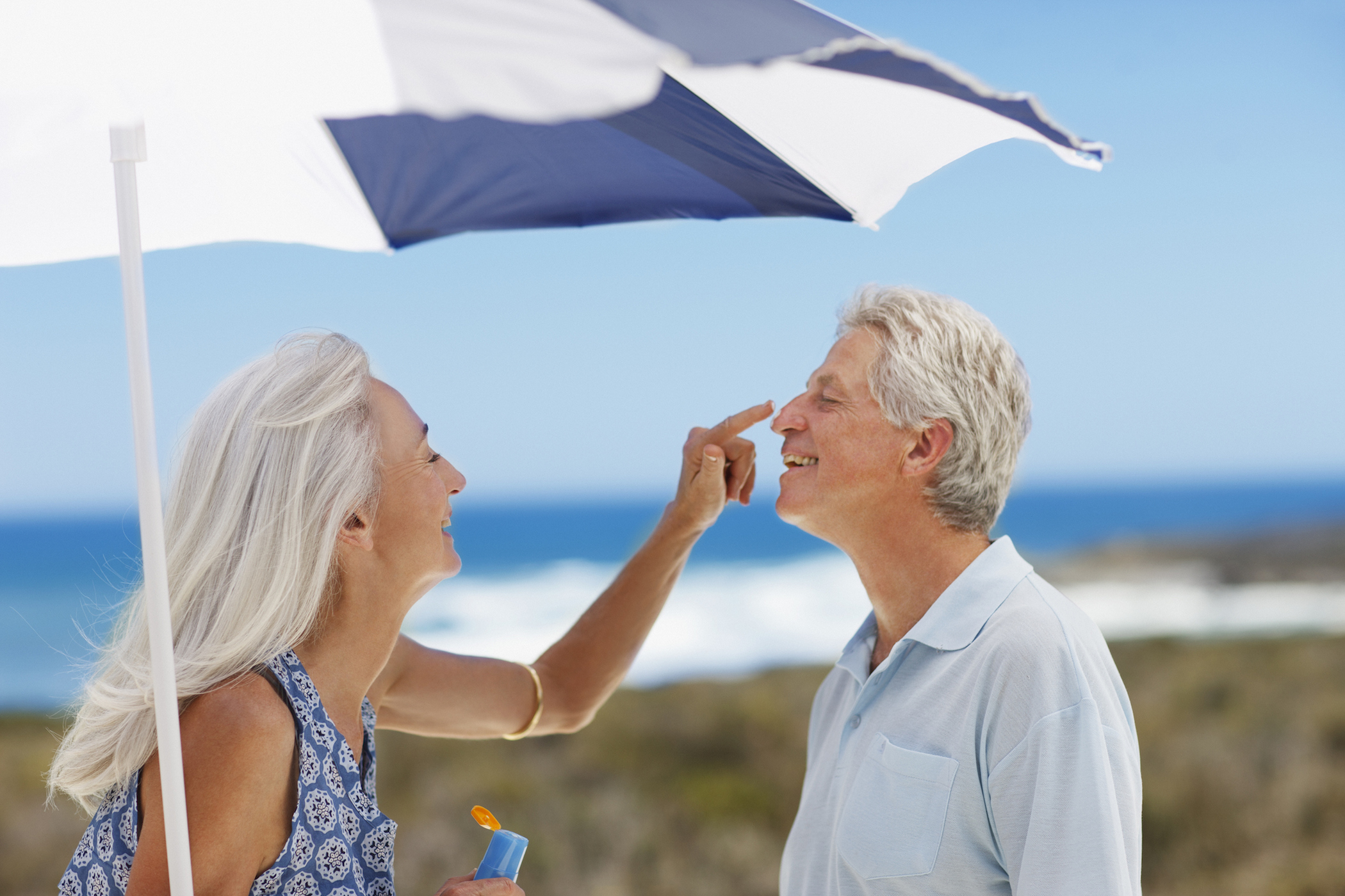 Senior woman applying sunscreen to mans nose