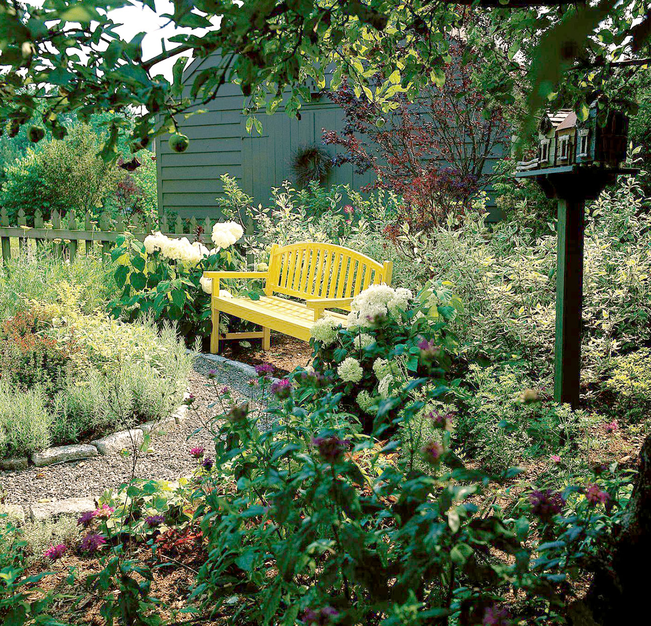 stone edging in garden with yellow bench