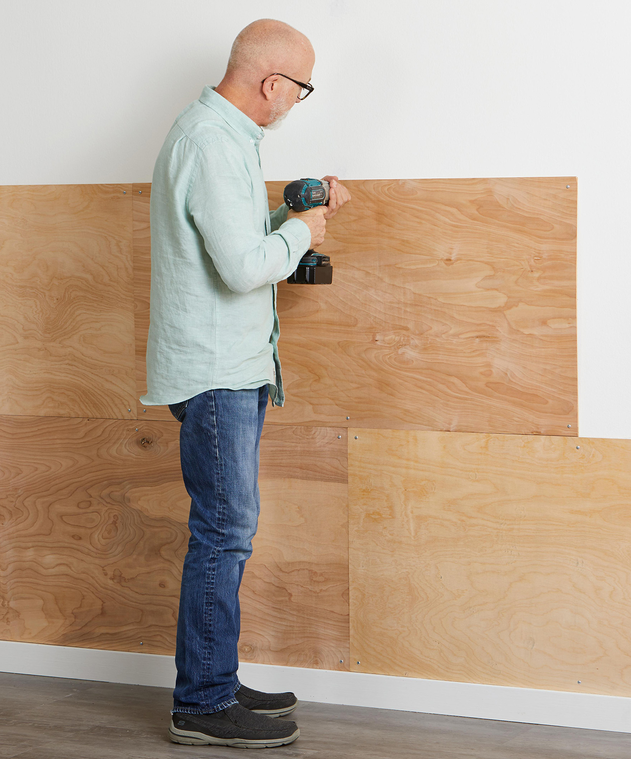 using electric drill to fasten plywood boards to walls