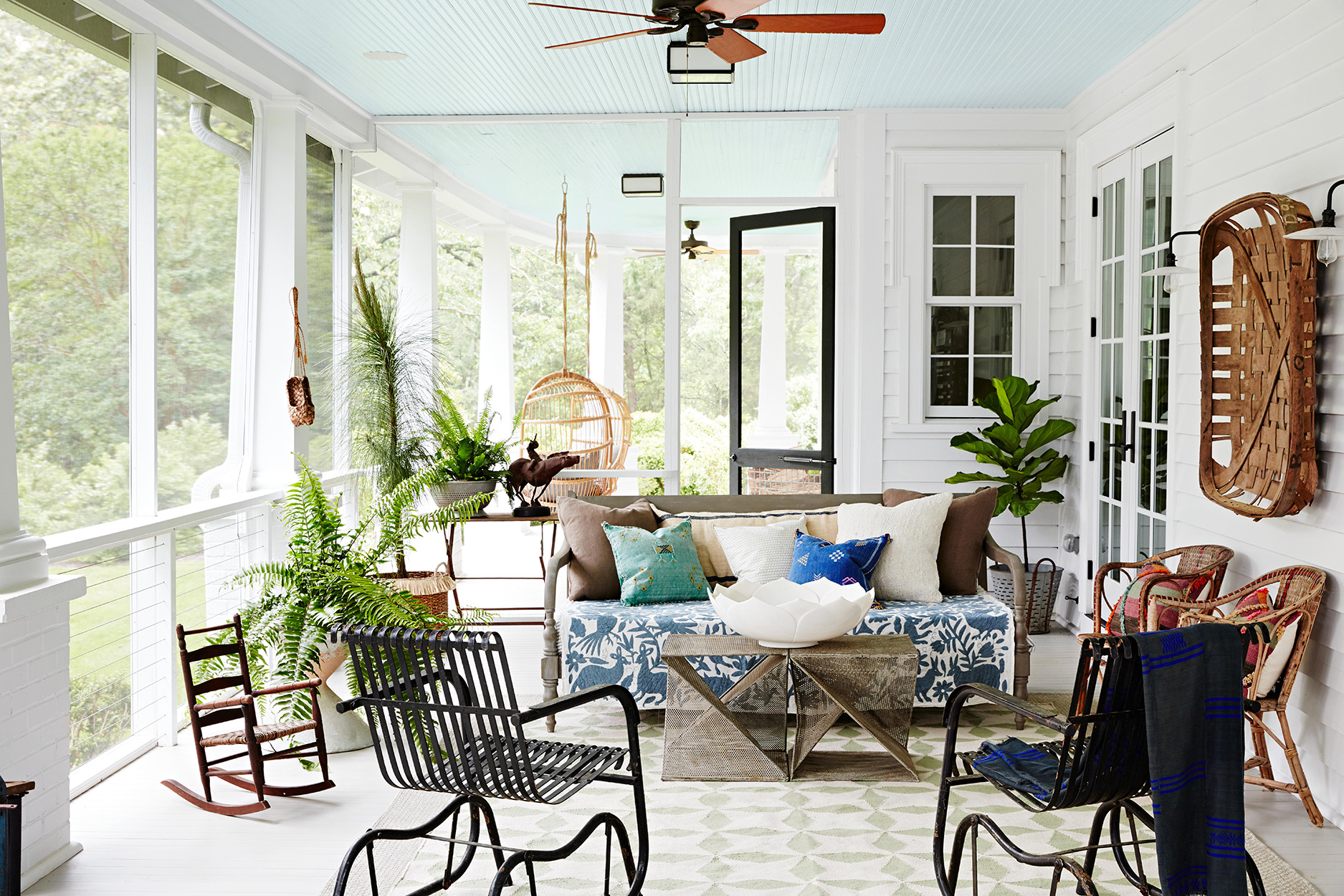 enclosed porch with black chairs and ferns